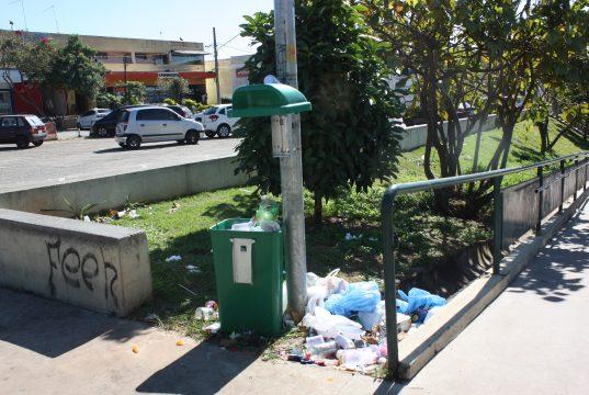 Lixeira quebrada e lixo acumulado